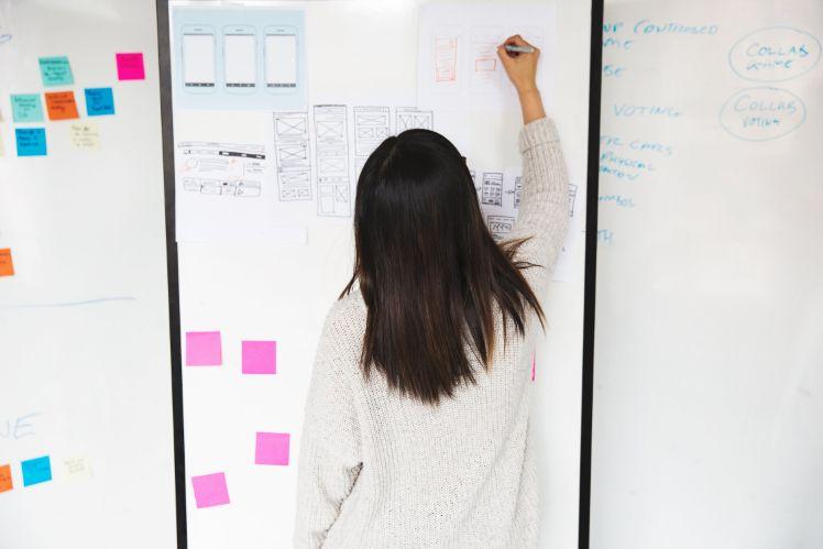 femme travaille sur un projet au tableau