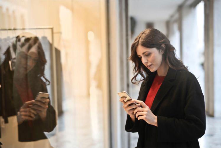 jeune femme avec smartphone devant vitrine