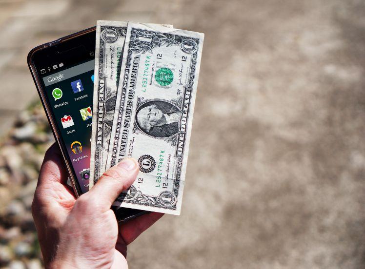 une main tient des dollars et un smartphone