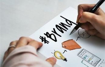 """écriture de """"brand"""" ,marque en gras avec un dessin d'ampoule sur une feuille blanche"""