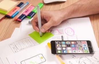 une main qui écrit sur un sticker vert, un smartphone a coté sur table et differents marqueurs de couleurs différentes