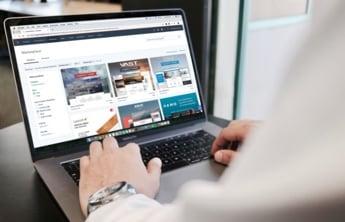 un homme qui travaille sur son pc portable qui affiche sur l'écran un site web