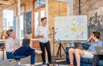 2 hommes présentant des informations sur un tableau blanc