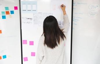 tableau blanc avec quelques stickers en couleurs et une jeune fille qui écrit sur tableau