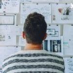 homme qui lit des papiers sur un mur