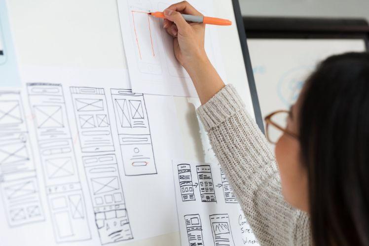 femme realise croquis design application sur un tableau blanc