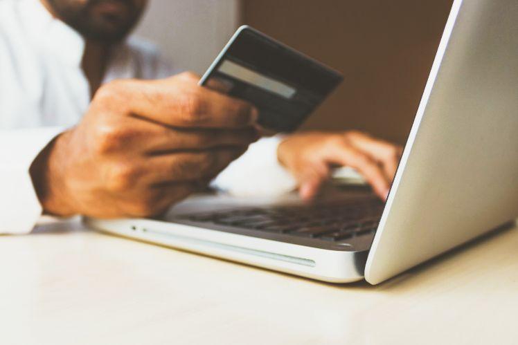 la main d'un homme tenant une carte bancaire et utilisant son pc portable