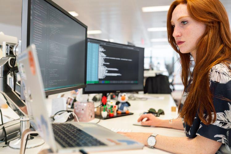 une femme travaillant sur 3 écrans,affichant differentes codes illustrant le principe d'automatisation intelligente des processus