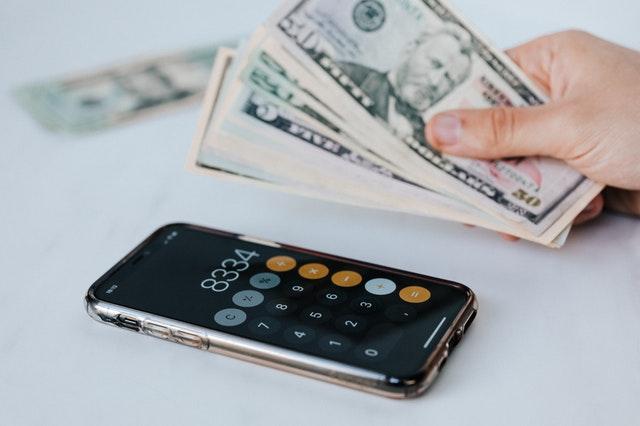 billets de monnaie et calculatrice sur téléphone