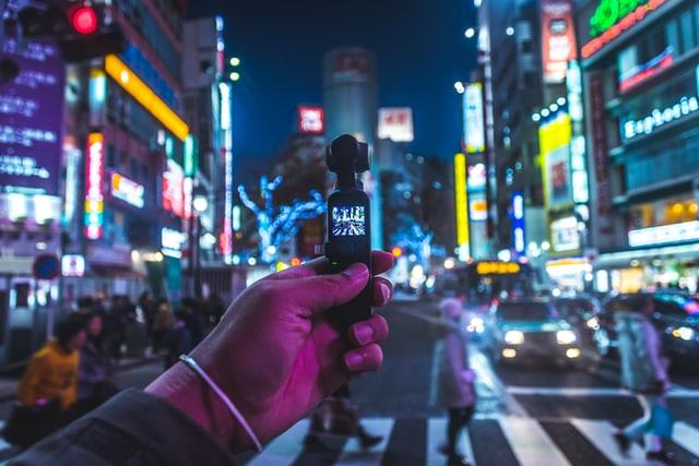 homme tenant un micro dans une ville éclairée